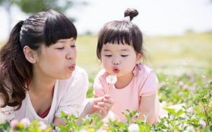 mom and girl blowing dandelions